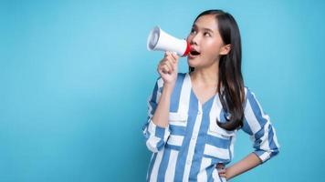 mujer asiática, tenencia, blanco, megáfono, con, un, fondo azul foto
