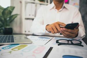 El empresario trabaja en el teléfono celular junto a la computadora portátil con papeles de tablas y gráficos