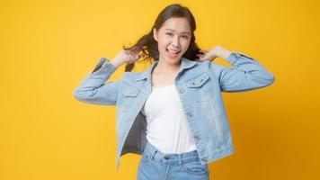 Asian woman smiling and playing with her hair on yellow background photo