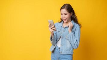 Mujer asiática sonriendo y mirando el teléfono celular sobre fondo amarillo