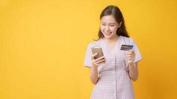 Asian woman smiling, holding credit card, and looking at cell phone on yellow background photo