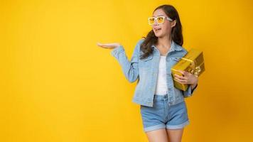 Mujer asiática sonriendo y sosteniendo una caja de regalo de oro sobre fondo amarillo foto