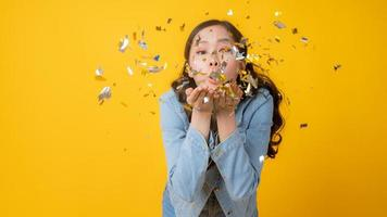 Asian woman blowing colorful confetti out of her hands and looking at the camera on yellow background photo