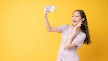 Mujer asiática sonriendo y tomando un autorretrato con un teléfono celular sobre fondo amarillo
