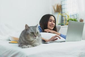 Mujer asiática trabajando en un portátil tendido junto al gato en la cama en el dormitorio