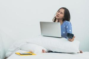 mujer asiática, con, computadora portátil, taza de café, gesticular, dolor de cuello, sentado, en cama foto