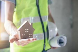 Trabajador de la construcción con casa modelo, casco y papeles enrollados o planos. foto