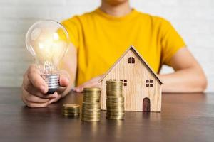 Person holding lit light bulb next to model house and stacks of coins photo