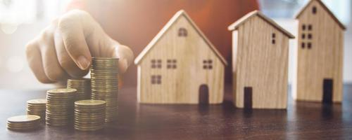 Person holding stacks of coins next to model house photo