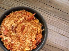 Paella and shrimp in a black bowl on a wooden table background
