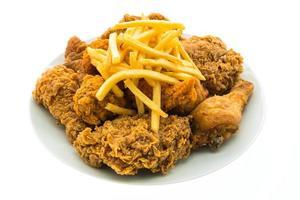 Pollo frito y papas fritas en una placa blanca.