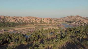 Paradisíaca orilla del río tungabhadra entre paisajes rocosos y exuberantes palmeras en hampi, india video