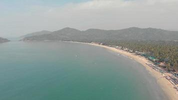 Turquoise ocean shore in Palolem Beach in southern Goa, India - Aerial Wide shot video