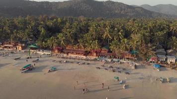 imagens de drones panorâmicas de uma praia ao pôr do sol em palolem, Índia, ocupadas com visitantes de todo o mundo video