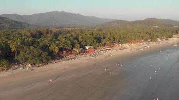 People stroll along Palolem beach sand and calming sea waves, Goa, India video