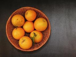 Mandarinas en un cuenco de mimbre sobre un fondo oscuro de la tabla foto