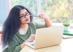 Mujer trabajando en una computadora portátil en casa durante el covid-19 foto
