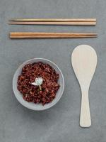 Top view of rice with chopsticks and wooden utensil photo