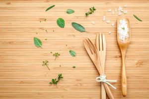 Sea salt and herbs with wooden utensils photo