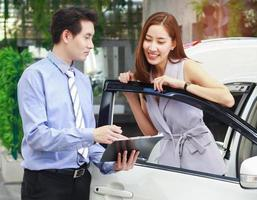 Salesperson and buyer in the car showroom center with a purchase contract photo