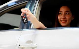 centrarse en las manos de una mujer con un coche nuevo en la sala de exposición foto