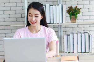 mujer asiática leyendo y haciendo los deberes