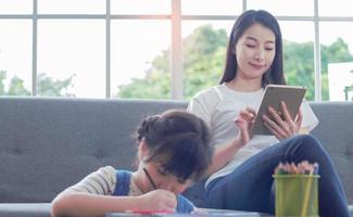 madre asiática felizmente se sienta enseñando a su hija a leer la tarea foto