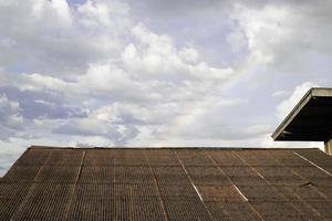 Clay roof with rainbow in the sky photo