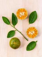 Naranjas frescas y rodajas de naranja sobre fondo de madera foto
