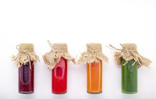 Colorful healthy smoothies and juices in bottles photo