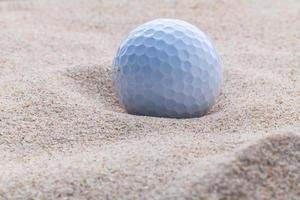 Golf ball in sand with copy space
