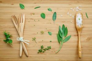 Herbs with wooden utensils and salt photo