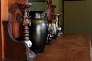 Vases and candlesticks next to a mirror on a dresser