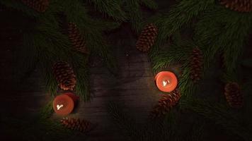 closeup animado vela de natal e galhos de árvores verdes em fundo de madeira