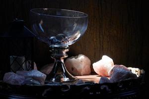 Pieces of rose quartz crystals under a spotlight next to a glass goblet