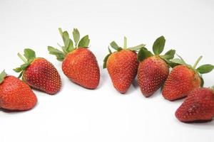 Row of strawberries on a white background