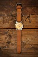 Analog wrist watch with brown dial and brown strap on wooden table