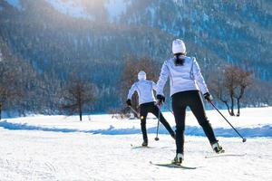 Pareja hombre y mujer esquiadores de fondo con técnica de patinaje foto