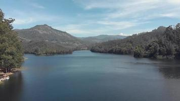Mattupetty in Munnar, surrounded by lush mountains and hills in India - Aerial Low angle Fly-over shot video