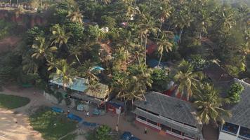 barracos e edifícios da praia de Varkala em meio à vegetação da costa tropical - foto de levantamento panorâmico de baixo ângulo video