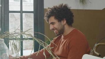 jonge man uit het Midden-Oosten zit aan tafel te kijken naar laptop voor hem, lacht video