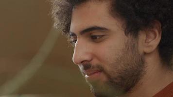 Nahaufnahme des jungen Mannes aus dem Nahen Osten, schaut auf Laptop, lächelt und spricht