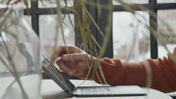 Nahaufnahme des jungen nahöstlichen Mannes, der am Tisch sitzt und Laptop-Bildschirm beobachtet und scrollt video
