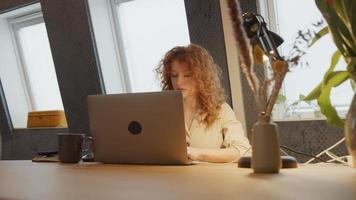 jonge blanke vrouw zit aan tafel, werkt op laptop, met behulp van de computermuis video