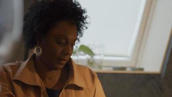 digitando as mãos no laptop de uma mulher madura negra focada sentada à mesa