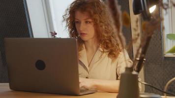 jovem mulher branca trabalhando em um laptop e conectando o cabo ao laptop