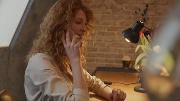 ung vit kvinna sitter vid bordet, börjar svara telefonsamtal video