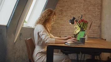 jovem mulher branca se senta à mesa, assiste laptop com tela verde