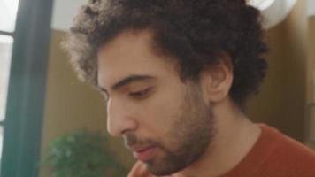 Der junge Mann aus dem Nahen Osten sitzt am Tisch und redet, während er auf dem Laptop tippt
