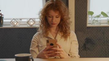 ung vit kvinna sitter vid bordet med mobiltelefon, skriver, vänder huvudet, ögonen ser in i kameran video
